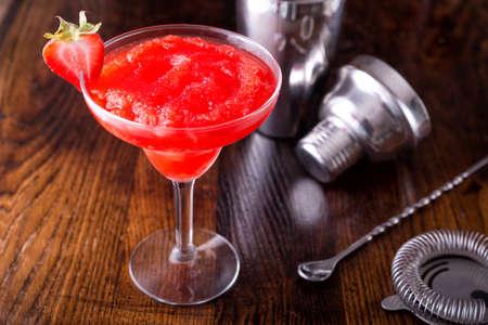 A delcious frozen strawberry daiquiri on a wooden bar counter top.