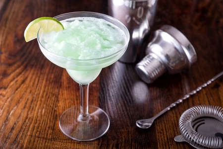 A delcious frozen lime daiquiri on a wooden bar counter top. 스톡 콘텐츠 - 126018095