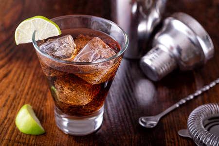 A delicious cuba libre cocktail on a wooden bar counter top.