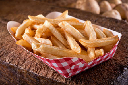 A serving of delicious french fries in take out container on a rustic wooden board.