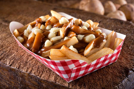 A serving of delicious poutine with french fries, cheese curds and gravy on a rustic wooden board. 스톡 콘텐츠