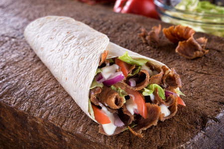 A delicious doner donair kebab wrap with spicy meat, lettuce, tomato, red onion and sauce.