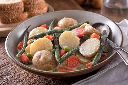 A delicious homemade Nova Scotia hodge podge vegetable stew with garden fresh potato, green beans, carrots and peas with cream. 스톡 콘텐츠 - 130049654