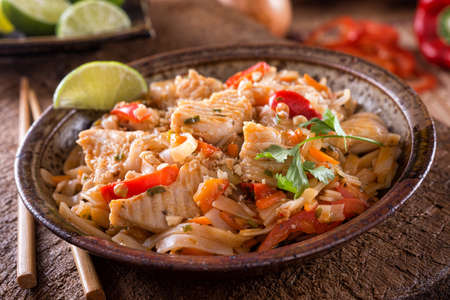 A bowl of delicious chicken pad thai with rice noodles, red bell pepper, peanut, carrot, ciliantro and lime. 스톡 콘텐츠