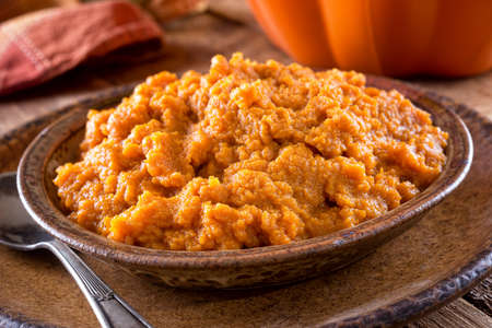 Freshly made mashed pumpkin puree in a bowl on a wooden table top.