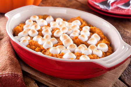 A delicious homemade sweet potato casserole with marshmallow topping. Foto de archivo