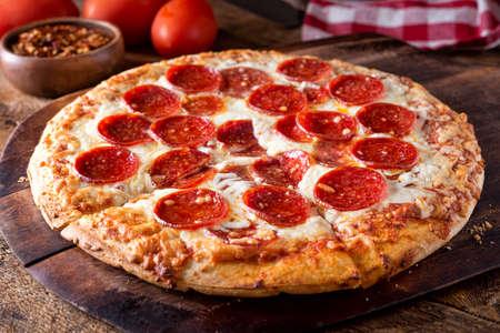 Een heerlijke pizza uit de steenoven gebakken pepperoni op een rustieke houten serveerplank.