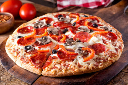A brick oven baked pizza deluxe with pepperoni, mushroom, red pepper, onion and black olives or a rustic wood board. 스톡 콘텐츠 - 131857965