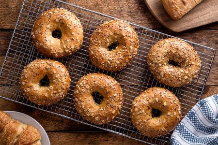 Freshly baked whole grain bagels cooling on a rack. 스톡 콘텐츠