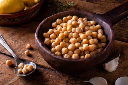 A bowl of chick peas on a rustic wood table top.