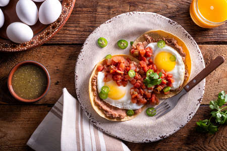 Delicious mexican style huevos rancheros with salsa, refried beans and corn tortilla.