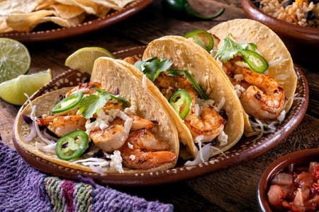 Delicious spicy shrimp tacos with shredded cabbage, queso fresco, and jalapeno pepper. 스톡 콘텐츠
