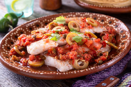 A plate of delicious fish veracruz with olives, tomato, onion, capers and serrano pepper. 스톡 콘텐츠 - 141322771