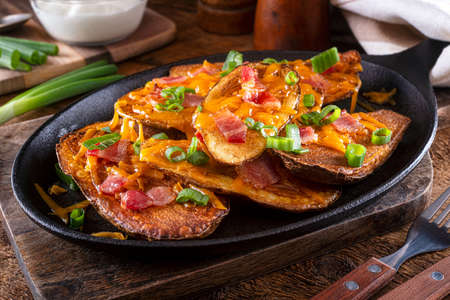 Delicious homemade potato skins with melted cheese, bacon, green onions and sour cream.