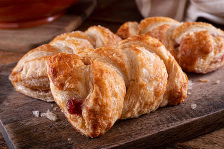 Delicious braided cherry mini strudels on a rustic wood counter top.