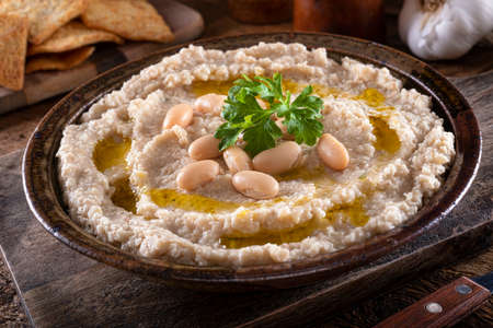 A bowl of delicious tuscan style white bean and garlic dip on a rustic table top. 스톡 콘텐츠 - 143343888