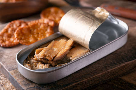 A can of smoked kippers and crackers on a rustic wood table top. 스톡 콘텐츠 - 144895621