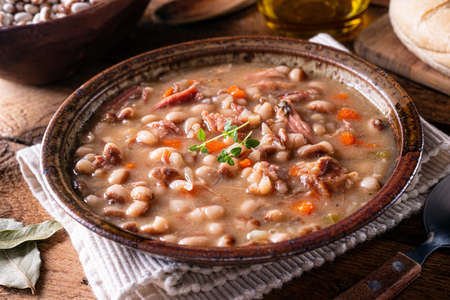 A bowl of delicious homemade bean soup with smoked ham and carrots.