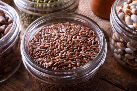 Brown flax seeds in a glass storage container. 스톡 콘텐츠