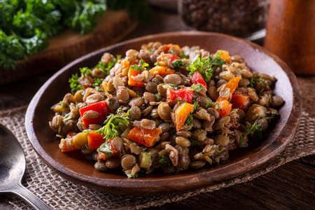 A bowl of delicious homemade mediterranean lentil salad with lentils, peppers, sun dried tomato and parsley.