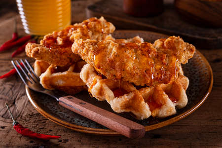 Delicious fried chicken and waffles with spicy hot honey sauce. 스톡 콘텐츠