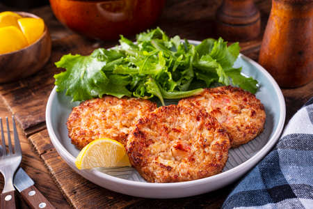 A plate of delicious crab cakes with spring mix salad and lemon garnish.