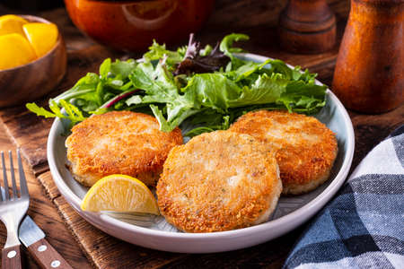 A plate of delicious fish cakes with spring mix salad and lemon garnish. Archivio Fotografico