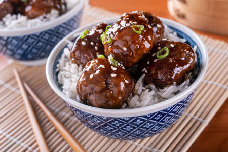 A bowl of delicious honey garlic meatballs with steamed rice. Stok Fotoğraf