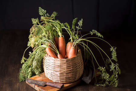 natural carrot inside a basket, on a wooden board, next to a razor and a dishcloth, on a dark background Stock Photo
