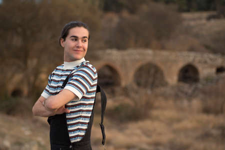 Young man posing in the field and with a bridge in the background. Enjoying the outdoors 스톡 콘텐츠