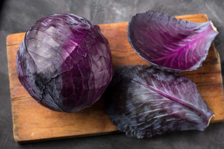 raw and whole purple Lombard on a wooden board on the table 스톡 콘텐츠