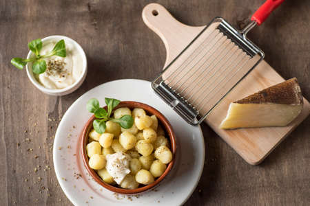 Delicious dish of round potato gnocchi accompanied by cheese sauce with the necessary accessories to taste them Zdjęcie Seryjne