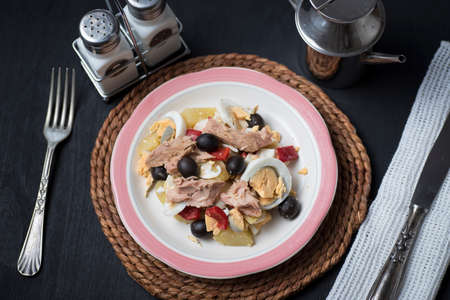 Potato salad with olives, tuna, boiled egg and its dressing. Delicious plate of Spanish food