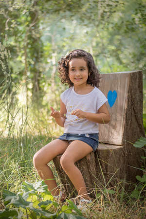 Girl in a white T-shirt and denim miniskirt sitting on a bench in a grove.