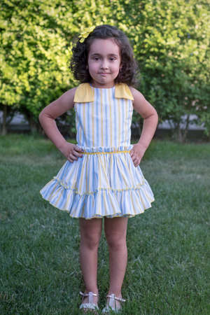 Girl posing in a yellow and blue striped dress in a green garden. Curly brown hair.