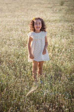 Little girl in the field on a summer afternoon defoliating a daisy. Curly black hair.