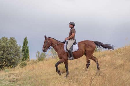 man riding a horse through a downhill field.