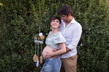 Young couple of pregnant woman and man on a green background Maternity.