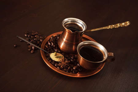 coffee pot: Still life, a copper coffee set consisting of a plate, a cezve, which is a turkish coffee pot, and a cup. The coffee pot is full of freshly brewed coffee. There are also coffee beans, a teaspoon of brown sugar and spices on the plate. Dark wooden backgrou
