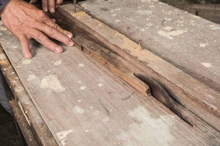 Asian carpenter Is sawing wood, Working hands with tools