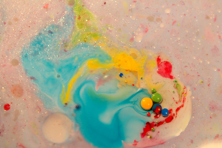 Abstract background, cyan and yellow color mix together in milk with small color dots. Macro photo
