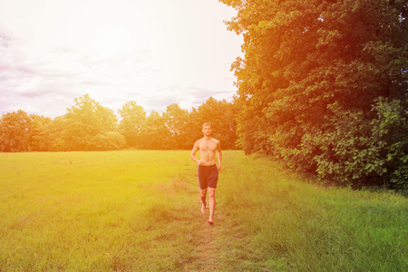 Young undressed man running in landscape with strong light.