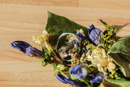 Wedding rings in dry flower on wooden background