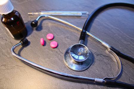 Estetoscopio, píldora, gota y termómetro, concepto médico Foto de archivo