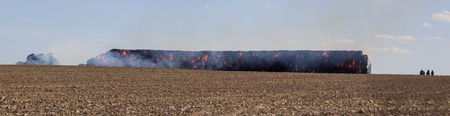 Panoramatic view to stack hay in fire on field with firemans