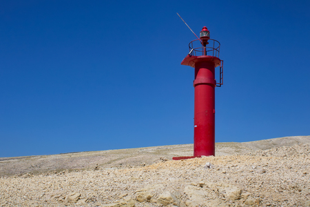 Red lighthouse on rock with blue sky, island Krk, Croatia