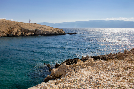 Cliff in sea with lighthouse and distant hill, island Krk, Croatia