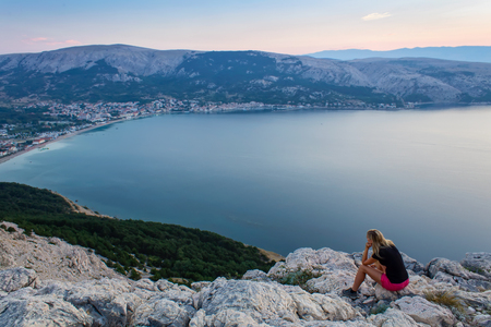 Young woman looking to sea and village Baska, island Krk Croatia