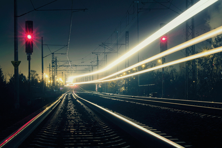 Sentier lumineux de train avec feu rouge, longue exposition