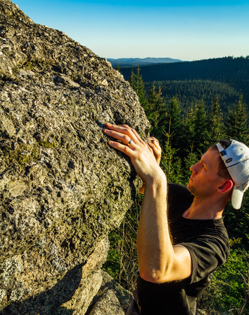 Young man in white cap climb on rock with forest and blue sky